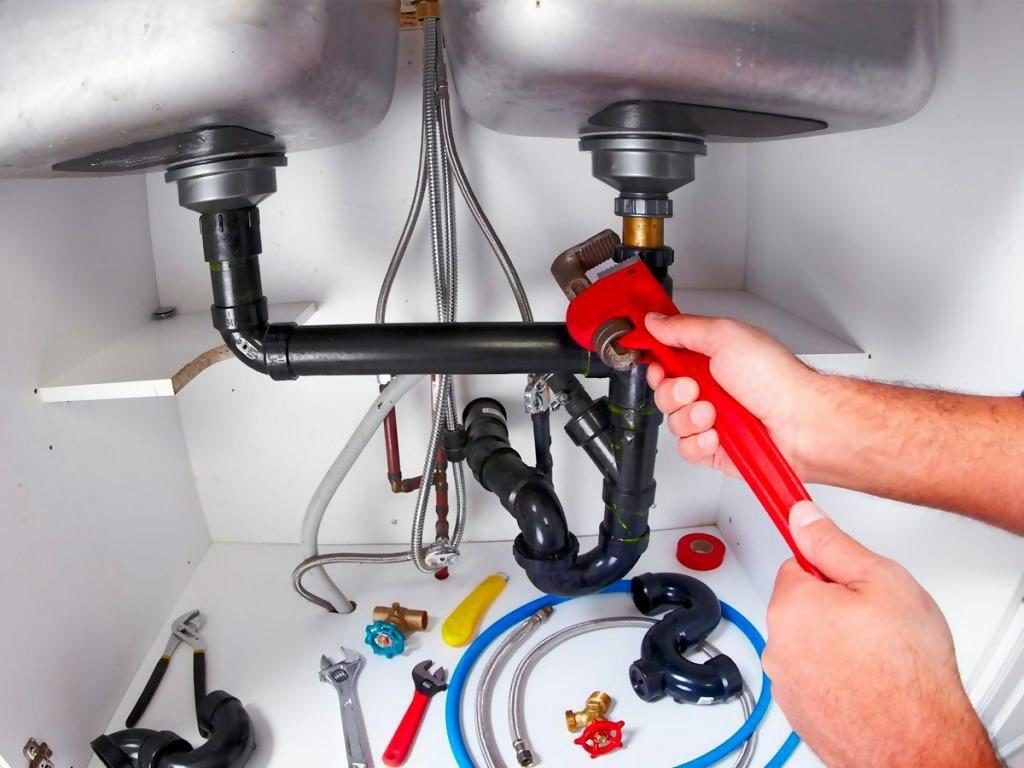Man using plunger for drain cleaning of bathroom sink