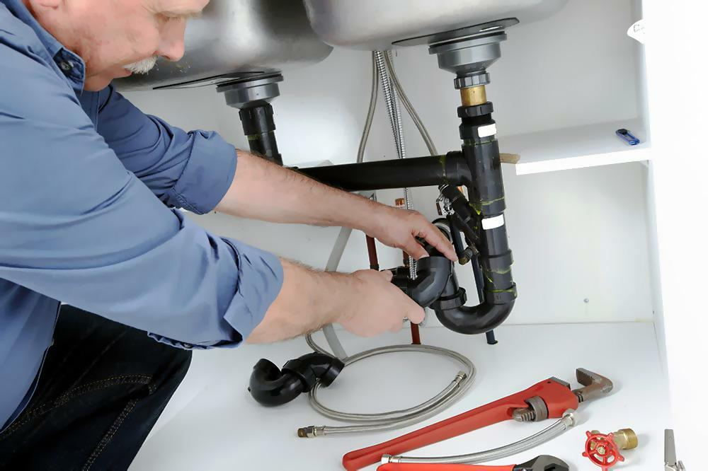 Plumbing carrying out drain cleaning on kitchen sink