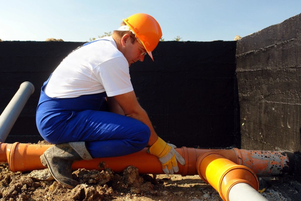 Experienced contractor carrying out sewer line repair