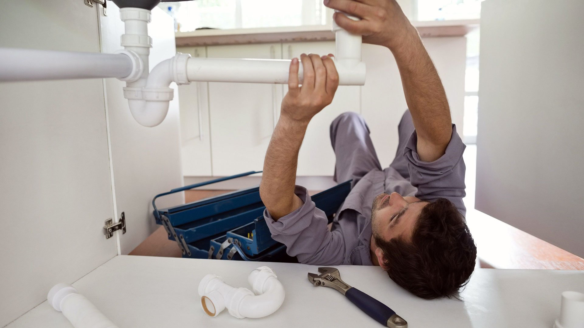 Plumber working on water line repair while under the sink